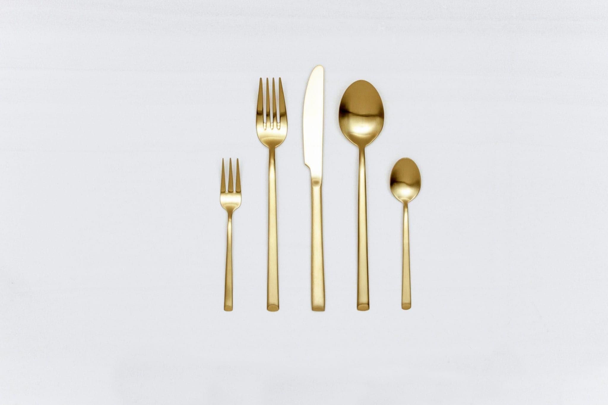 Besteck Set Ines Gold Matt 5-teilig | Mit der Besteckserie Ines vermieten wir herrlich, matt goldenes Edelstahlbesteck. Das Besteck hat eine schöne Haptik und sieht zu unterschiedlichen Events gleichermaßen gut aus. Ob auf einem bunten Tisch mit kräftigen Farben kombiniert, einer eleganten, minimalistischen Hochzeit oder einem modernen Business Dinner - unser matt goldenes Besteck Ines ist eine ausgzeichnete Wahl für Deinen Event. Das zusammengestellte Set Mietbesteck besteht aus einer Gabel, einem Messer, einem Suppenlöffel, einer Kuchengabel und einem Teelöffel. Begeistere Deinen Gäste, miete das 7-teilige goldene Besteckset Ines und kombiniere es mit unserem vintage Geschirr. Passend zum goldenen Besteck Ines bieten wir auch Teelöffel, Tortenheber, Servierlöffel, Espressolöffel, Buttermesser und vintage Weingläser im Verleih an. | gotvintage Rental & Event Design