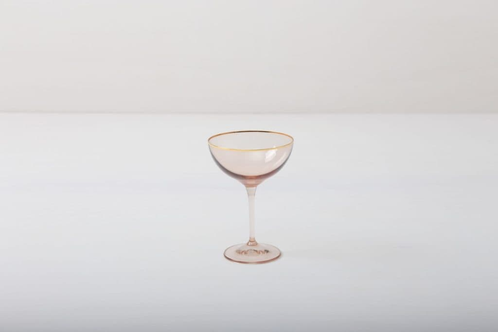 Champagne Coupe Acadia Blush Gold Rim 21cl | This champagne coupe with gold rim and slightly tinted light pink glass adds to every dinner or reception. You can use it for champagne or cocktails. Obviously, you can just drink water from it, too.The full set contains water tumbler, white wine glass, red wine glass, champagne flute and champagne coupe. | gotvintage Rental & Event Design