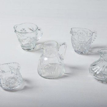 Diese Milch- und Sahnekännchen aus vintage Kristallglas verleihen dem festlichen gedecktem Tisch einen romantischen Look. Mit ihren zarten Verzierungen und der wunderschön geschwungenen, bauchigen Form vervollständigen sie jede Kuchentafel. Geeignet sind sie außerdem als wunderschöne, kleine Blumenvasen. Passend zu den Milchkännchen haben wir auch Zuckerdosen und zahlreiche Vasen und Schalen aus Kristall.
