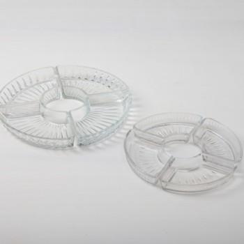Diese zarten, trapezförmigen Pressglasschälchen ergeben zusammengestellt einen dekorativen Kreis, in dem sich die leckersten Snacks, ob süß oder salzig, hervorragend präsentieren. Ob auf einer Hochzeit oder Weihnachtsfeier, aus den Schälchen schmecken kleine Pralinen, Bonbons, Nüsse oder Oliven immer besonders köstlich. Die Kristallschalen machen sich auf dem Barwagen, einer langen Tafel oder der Candy-Bar gleichermaßen gut. Schön dazu sind unsere Kristallkaraffen und anderen Schälchen im Vintage-Kristall-Stil.
