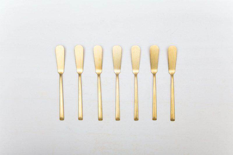 Buttermesser Ines Besteck Gold Matt | Mit der Besteckserie Ines vermieten wir herrlich, matt goldenes Edelstahlbesteck. Das Besteck hat eine schöne Haptik und sieht zu unterschiedlichen Events gleichermaßen gut aus. Ob auf einem bunten Tisch mit kräftigen Farben kombiniert, einer eleganten, minimalistischen Hochzeit oder einem stylischen Business Dinner - unser matt goldenes Besteck Ines ist eine ausgzeichnete Wahl für Deinen Event. Mit dem Buttermesser Ines lässt sich die Butter elegant auf jedem Brot und Brötchen verteilen. Ein Buttermesser sollte bei einem mehrgängigen Menü nicht fehlen. Miete die Buttermesser Ines, um in Ergänzung mit dem goldenen Besteck, Deine Gäste zu begeistern. Passend zu den matt goldenen Buttermessern Ines bieten wir auch Besteck für Vorspeisen, Hauptgang, Dessert, Brotteller mit Goldrand und vintage Geschirr im Verleih an. | gotvintage Rental & Event Design