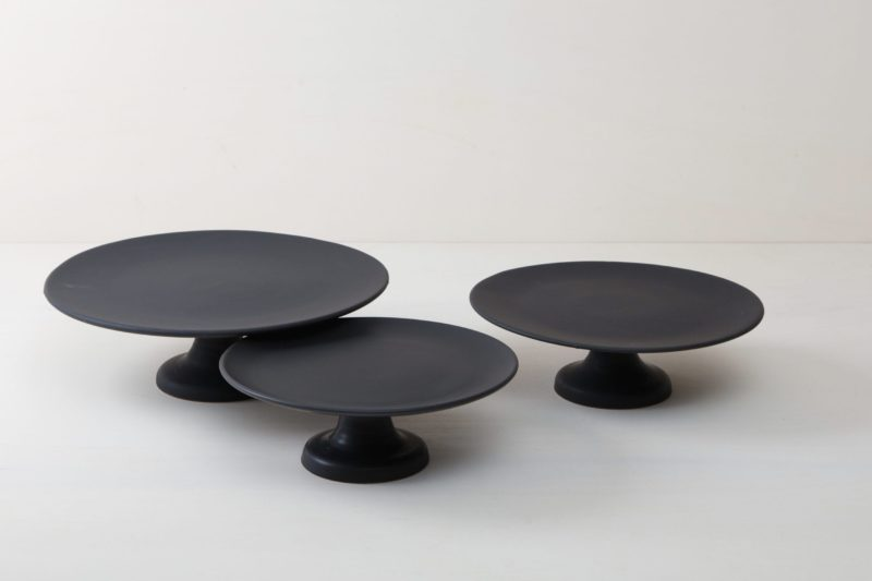| Our medium size elevated cake stand Ernesta rests on a 13 cm high foot and has a diameter of 35 cm. On the matt black serving tray there is enough room to present and arrange cakes, cupcakes, sushi and other delicacies on the table or at the modern buffet. The serving trays are handcrafted from high-quality terracotta and glazed matt black, obviously food safe.These cake stands are available in three different sizes as well as a matt white serving tray. They can be wonderfully combined for p... |