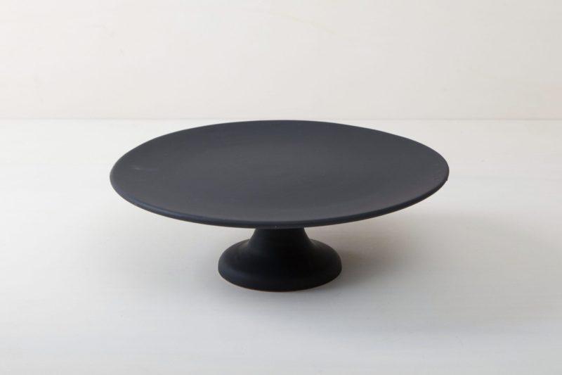 Tortenständer Ernesta Schwarz Matt XL | Unser großer runder erhöhter Tortenständer Ernesta steht auf einem 15 cm hohen Fuß und hat einen Durchmesser von 40 cm. Auf der matt schwarzen Servierfläche gibt es genug Platz zum Präsentieren und Arrangieren von Kuchen, Cupcakes, Sushi und anderen Köstlichkeiten auf dem Tisch oder am modernen Buffet. Die Servierplatten wurden aus hochwertigem Terrakotta Handgefertigt und matt schwarz glasiert, natürlich lebensmittelecht. Diese Tortenständer gibt es in drei verschiedenen Größen sowie als matt weiße Servierplatte. Sie lassen sich wunderbar kombinieren und variieren. | gotvintage Rental & Event Design