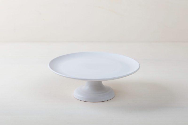 Tortenständer Ernesta Weiß Matt M | Unser kleiner erhöhter Tortenständer Ernesta steht auf einem 12 cm hohen Fuß und hat einen Durchmesser von 32 cm. Platz zum Präsentieren und Servieren von Kuchen, Cupcakes, Sushi und anderen Köstlichkeiten auf dem Tisch oder am modernen Buffet. Die Servierplatten wurden aus hochwertigem Terrakotta Handgefertigt und matt weiß glasiert, natürlich lebensmittelecht. Diese Tortenständer gibt es in drei verschiedenen Größen sowie als matt schwarze Servierplatte. Sie lassen sich wunderbar kombinieren und variieren. | gotvintage Rental & Event Design