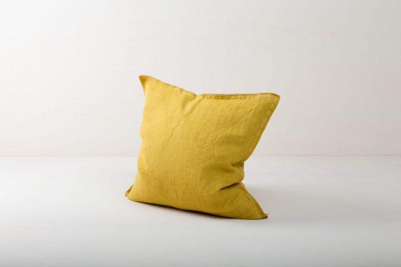 Kissen Cosme Leinen Ochre 50x50 | Schönes gelbes Kissen aus steingewaschenem Leinen. Der Leinenstoff ist vorgewaschen und hat dadurch diesen modernen Look von stonewashed Leinen und ist auch sehr weich. Die Kissen in verschiedenen Farben aus unserem Verleihkatalog können hervorragend miteinander kombiniert werden. Mit den Leinenkissen Cosme lassen sich im Handumdrehen Events, Sofas oder Lounges verschönern. Der Reißverschluss bei diesen Leinenkissen ist verdeckt eingenäht, das macht jede Seite der Kissen aus Leinen gleich dekorativ. Wir lieben den natürlichen und zugleich rustikalen Look von stonewashed Leinen und die Kombination mit anderen Farben und Formen sehr. | gotvintage Rental & Event Design