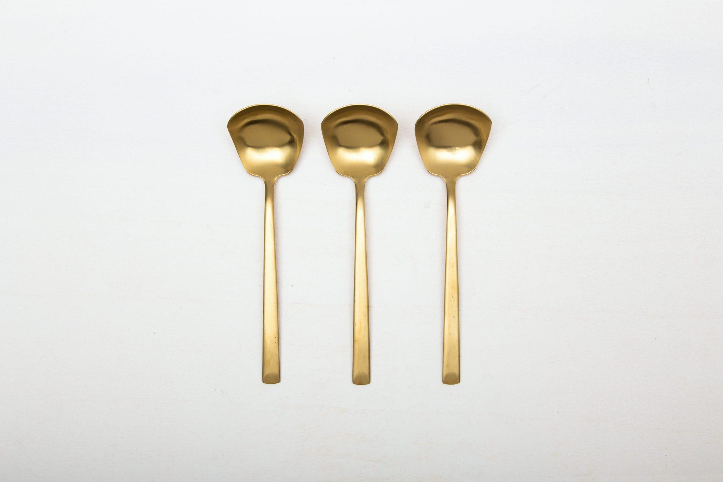 Saucenlöffel Ines Besteck Gold Matt | Mit der Besteckserie Ines vermieten wir herrlich, matt goldenes Edelstahlbesteck. Das Besteck hat eine schöne Haptik und sieht zu unterschiedlichen Events gleichermaßen gut aus. Ob auf einem bunten Tisch mit kräftigen Farben kombiniert, einer eleganten, minimalistischen Hochzeit oder einem stylischen Business Dinner - unser matt goldenes Besteck Ines ist eine ausgzeichnete Wahl für Deinen Event. Miete die Saucenlöffel Ines, um in Ergänzung mit dem goldenen Besteck, Deine Gäste zu begeistern. Passend zu den matt goldenen Saucenlöffeln Ines bieten wir auch vintage Geschirr und vintage Servierschüsseln im Verleih an. | gotvintage Rental & Event Design