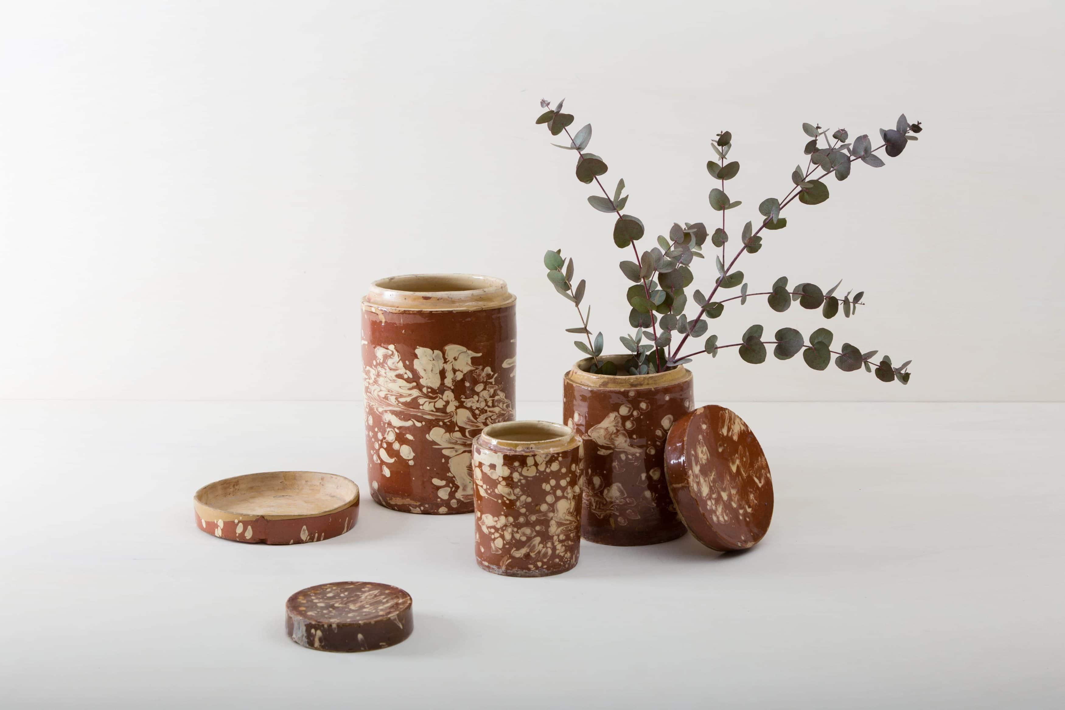 """Diese besonderen Vasen der Serie Punca sind ganz individuell und interessant bräunlich marmoriert. Gemeinsam geben sie ein harmonisches Bild ab und sehen zu Herbst wie Sommerevents gleichermaßen gut aus. Ob als Vase für einen tollen Frühlings- oder Kornblumenstrauß oder aber als Süßigkeitendose auf dem Buffettisch– Vase Punca ist abwechslungsreich und mal """"etwas anderes"""". Braun marmorierte Keramik, die alte Technik der Marmorglasur ist in Süditalien sehr beliebt. Die zylindrischen Vorratsgefässe stammen aus den 1930er Jahren und es wurden darin Antipasti oder Oliven gelagert. Nun gut gereinigt kannst Du die Gefäße als Vase für Dein Eventstyling oder Hochzeitsdekoration einsetzen."""